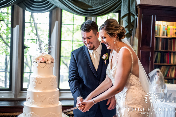 cheerful bride and groom cake cutting ceremony at reception hall wedding photos