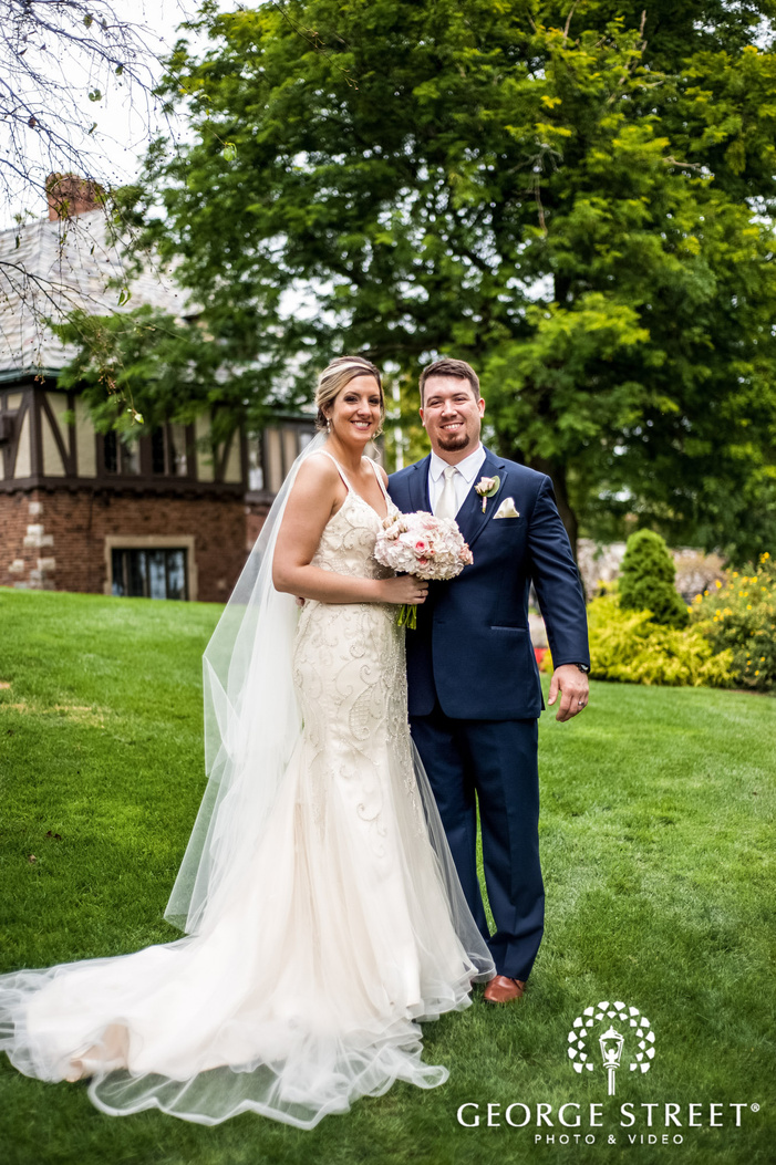 cheerful bride and groom outside pine knob mansion in detroit wedding photos