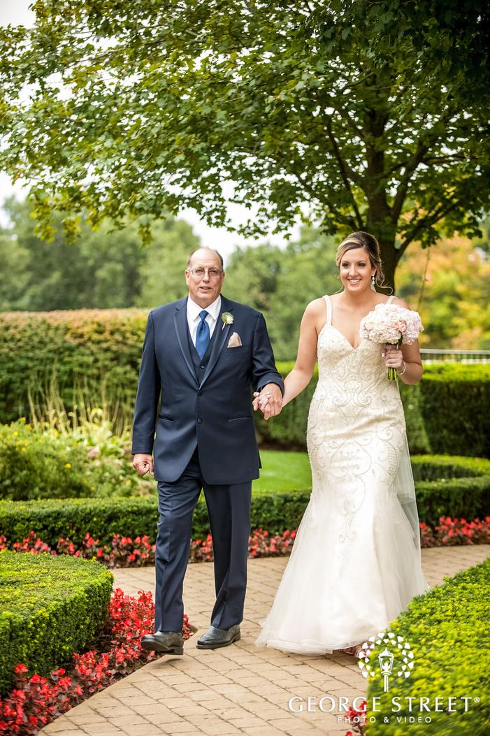 happy bride and father walking towards the wedding ceremony wedding photo