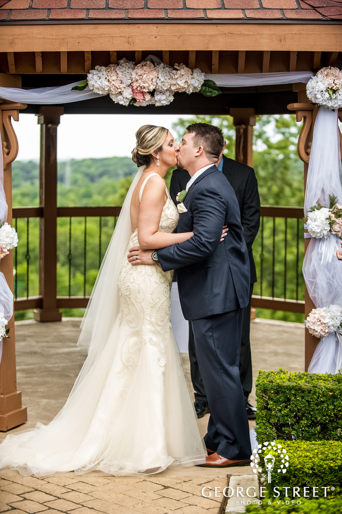 loving bride and groom first kiss at wedding altar