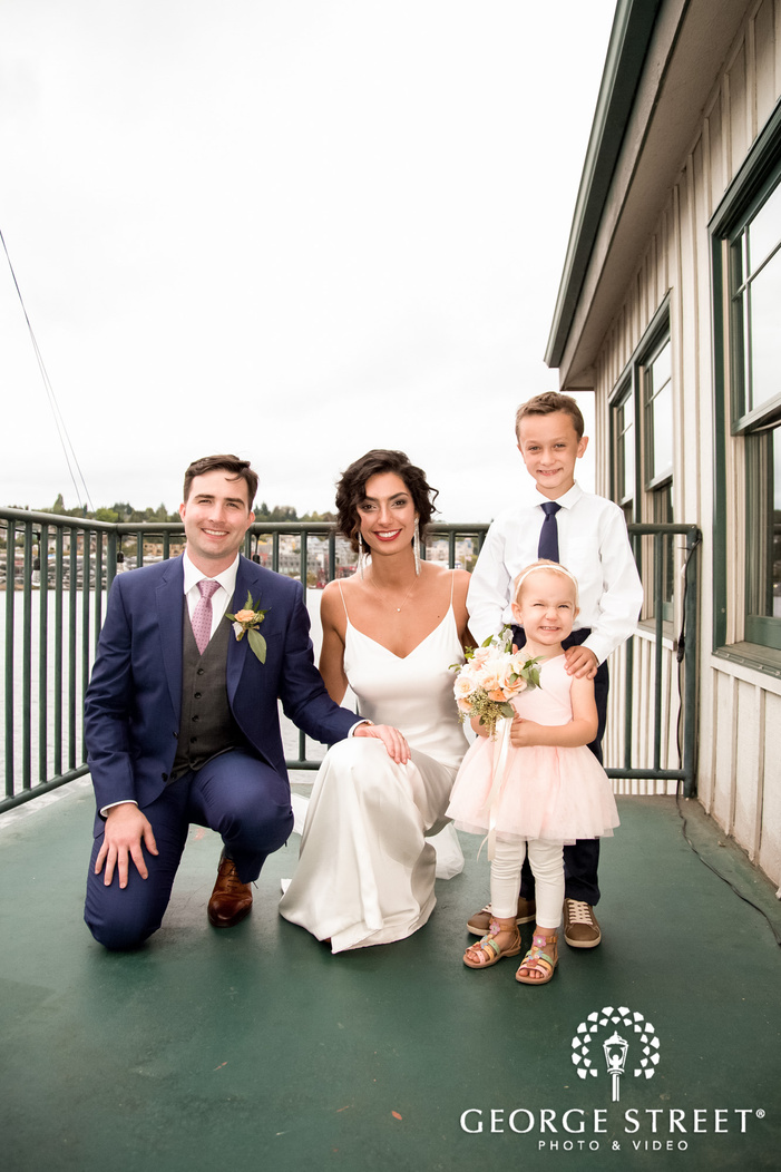 cute bride and groom with child at riverside
