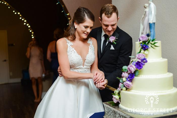 joyful bride and groom cake cutting in reception wedding photo