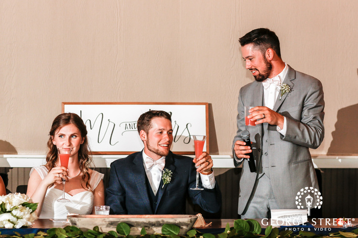 cheerful bride and groom during reception toast