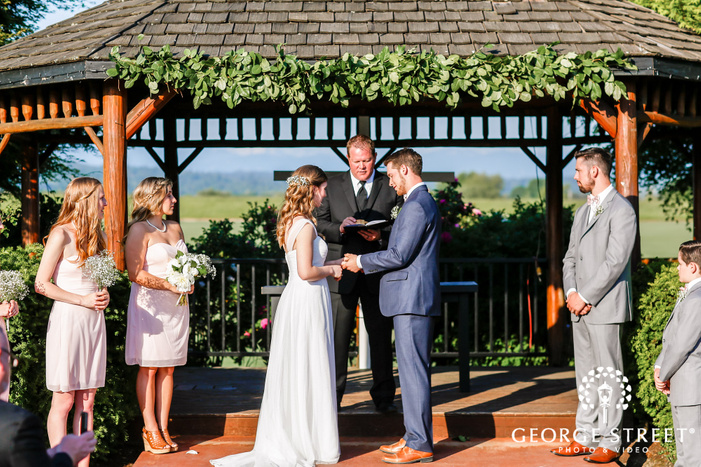 goegeous bride and groom rings exchange ceremony at altar
