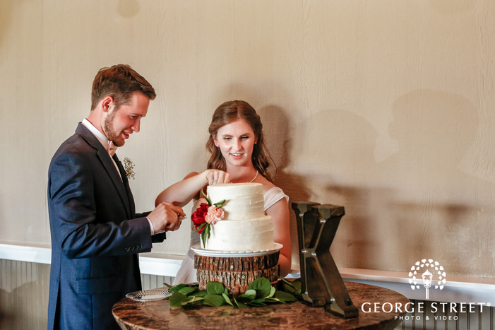 pretty bride and groom at cake cutting ceremony