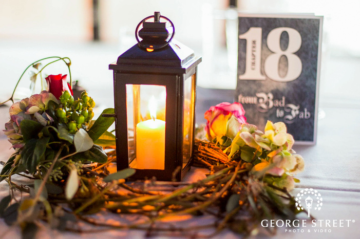black lantern surrounded by flowers and table number reception decor