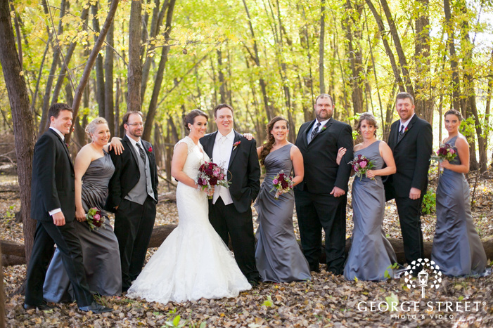 bridal party with bride and groom in wooded area with fall leaves