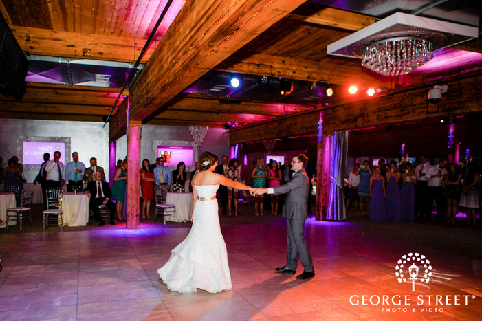 bride and groom first dance in colorful reception space