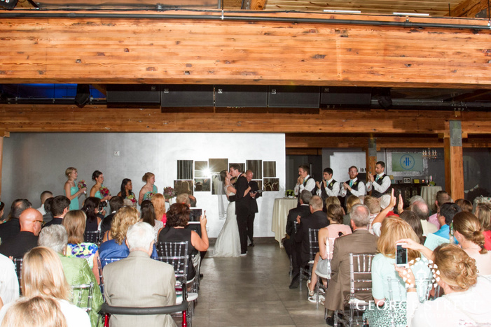 bride and groom first kiss at indoor wedding ceremony
