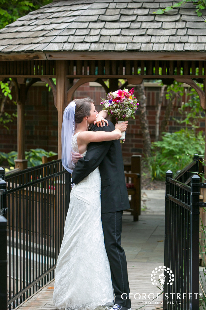 bride and groom hugging by outdoor gazebo after first look