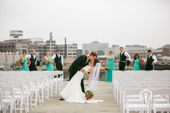 bride and groom kissing in front of bridal party at rooftop wedding ceremony