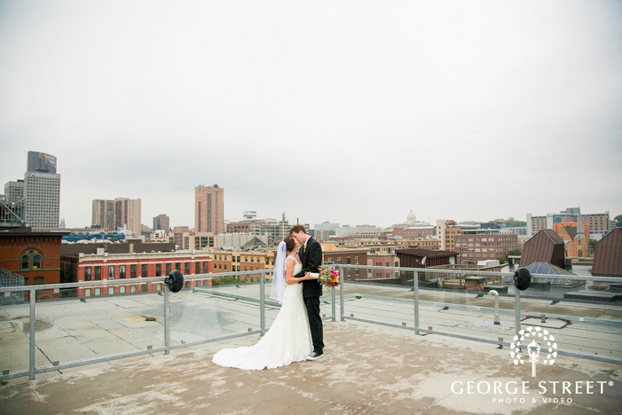 bride and groom kissing on rooftop with city in background
