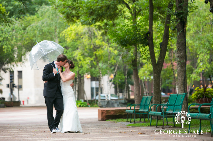 bride and groom kissing under umbrella in bright outdoor courtyard with green benches