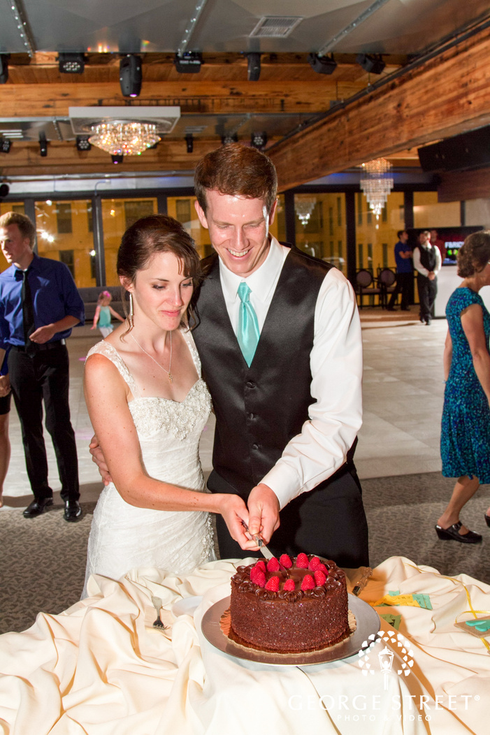 bride and groom smiling and cutting chocolate cake at wedding reception