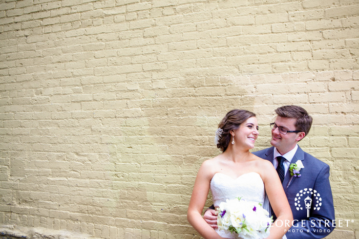 bride and groom smiling and looking at each other in front of brick wall
