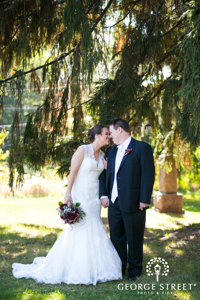 bride and groom smiling and touching noses under large pine tree