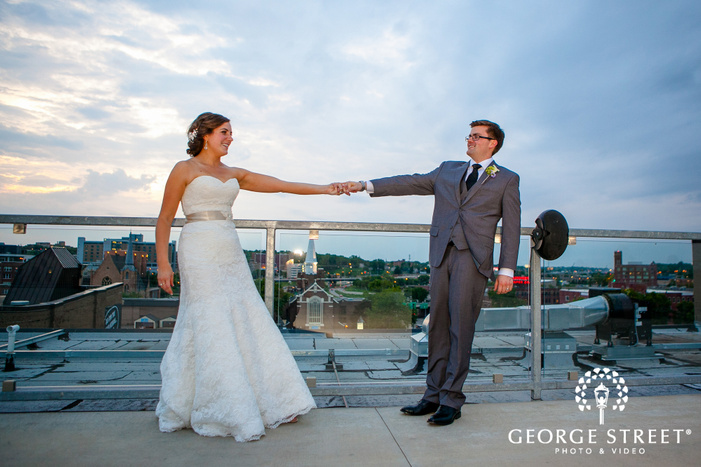 bride and groom standing on rooftop in front of city background