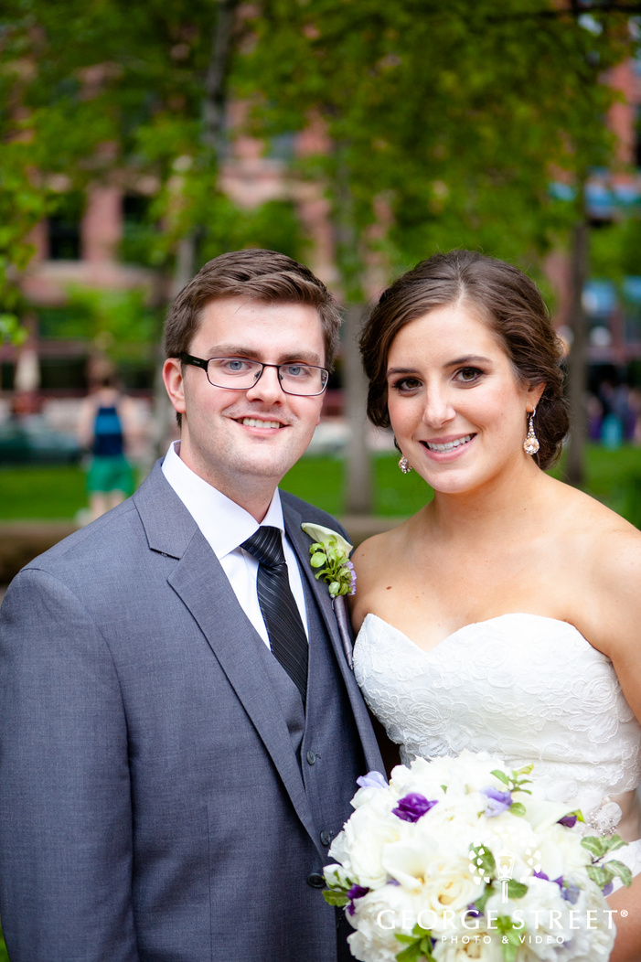 bride holding bouquet and smiling with groom outdoors
