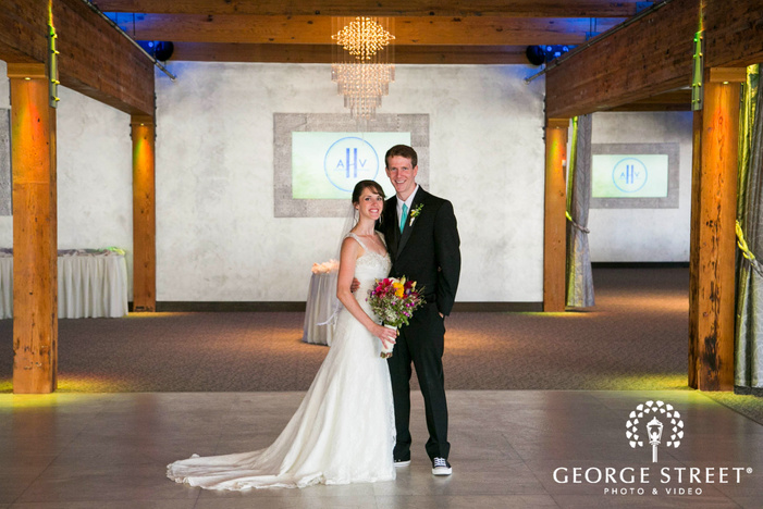 bride holding bouquet smiling with groom inside of reception venue