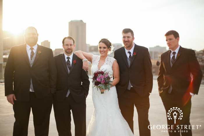 bride holding bouquet with groomsmen on rooftop with sunflare