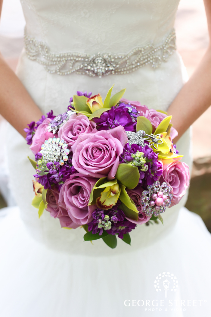 bride holding pink and purple bouquet with crystal brooches