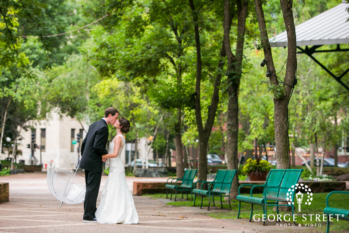 bride kissing groom holding an umbrella in bright green outdoor courtyard