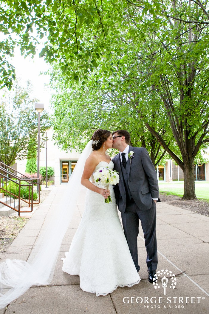 bride kissing groom outside of venue surrounded by trees