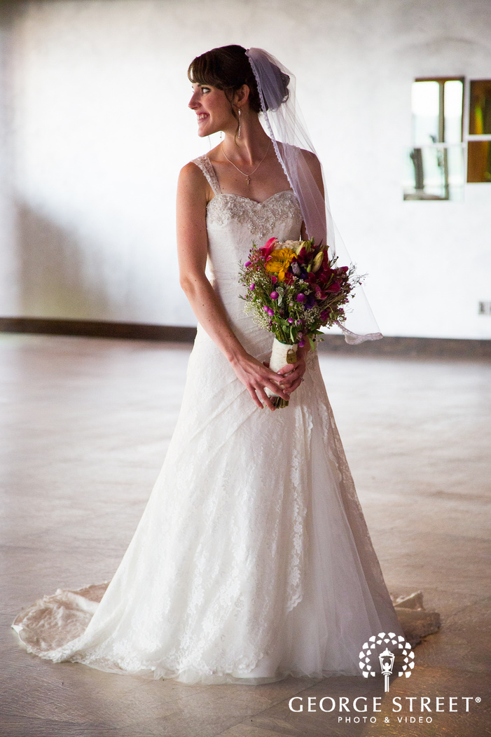 bride looking to side holding large bouquet in white reception room