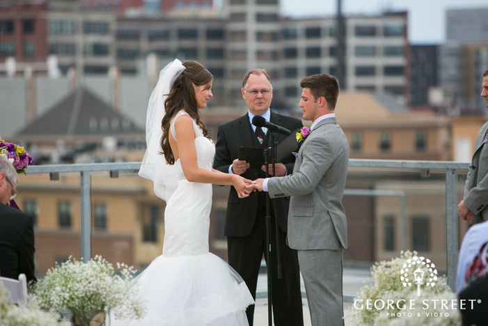 bride putting ring on grooms finger in rooftop wedding ceremony