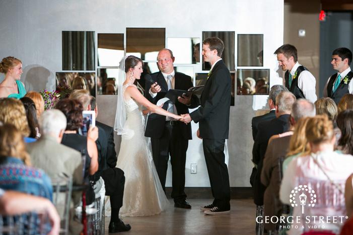 bride reading vows to groom at indoor wedding ceremony
