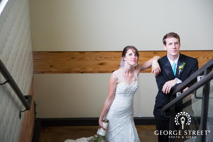 bride resting arm on grooms shoulder in stairwell