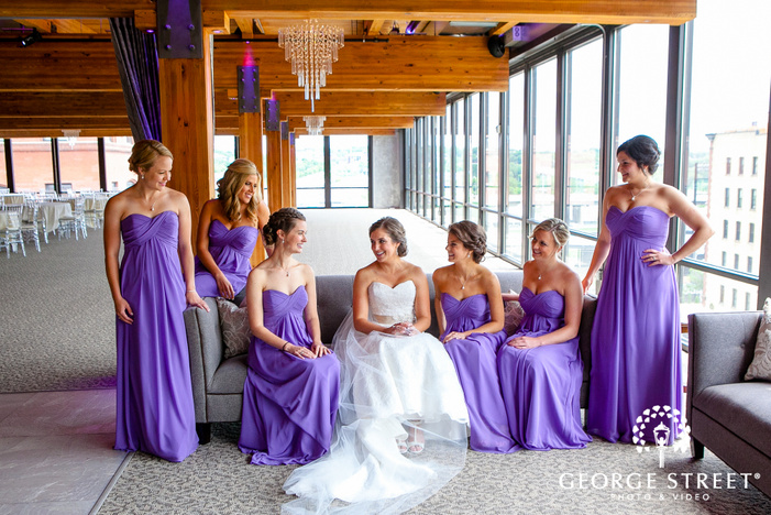 bride sitting with bridesmaids by wall of windows in reception