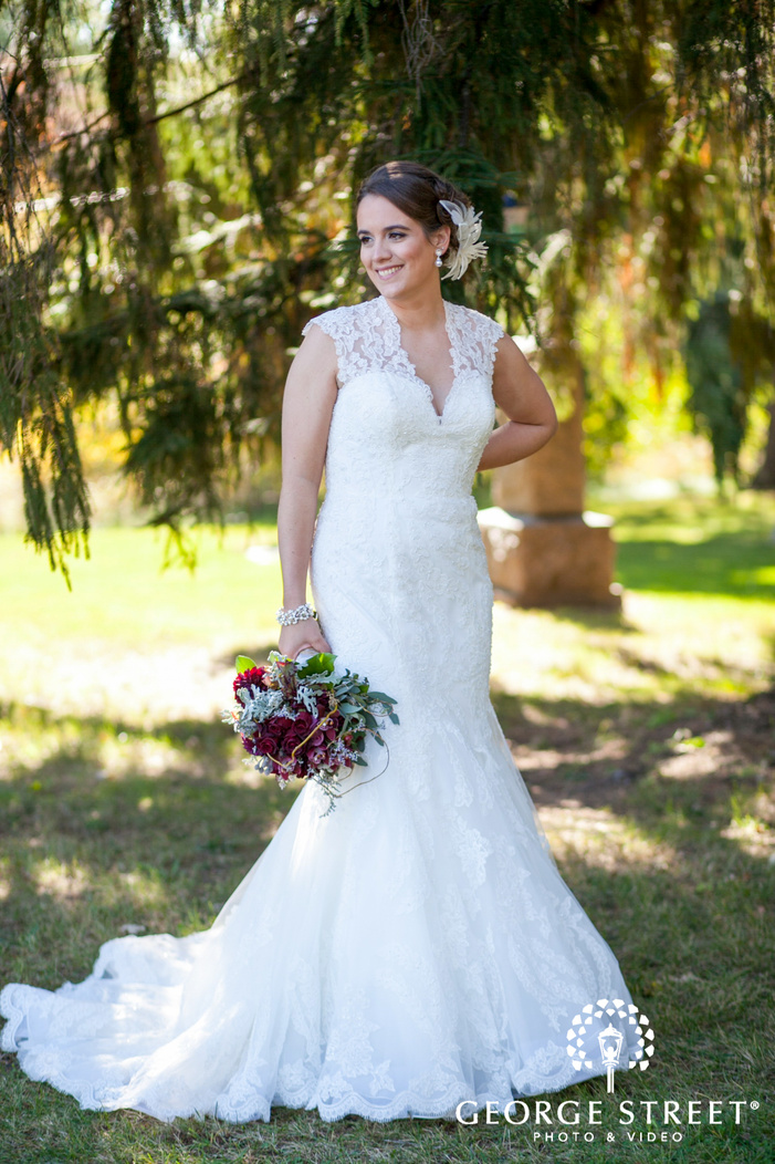 bride smiling with bouquet under large pine tree