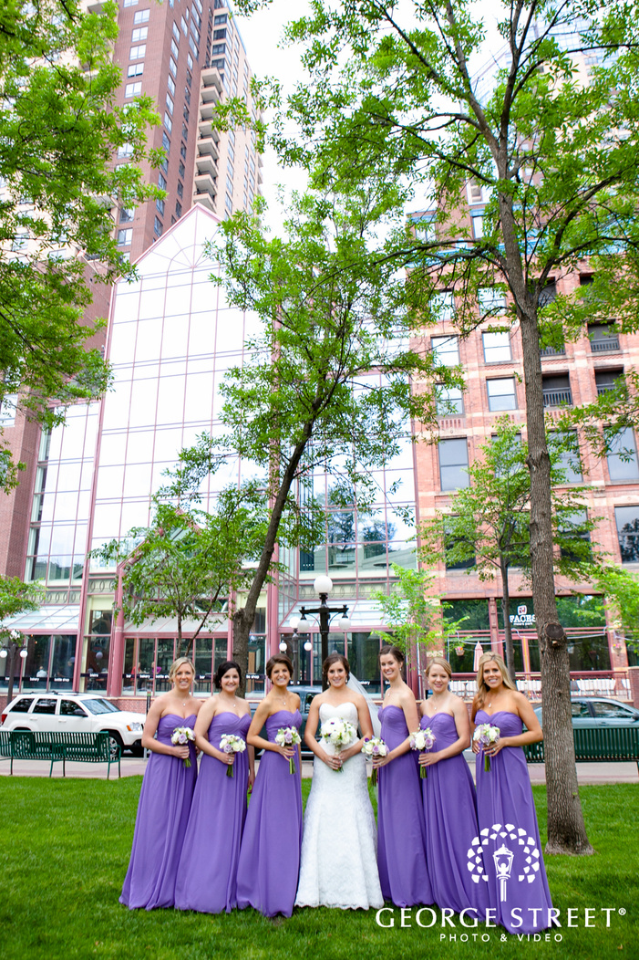 bride standing with bridesmaids in front of trees and glass building