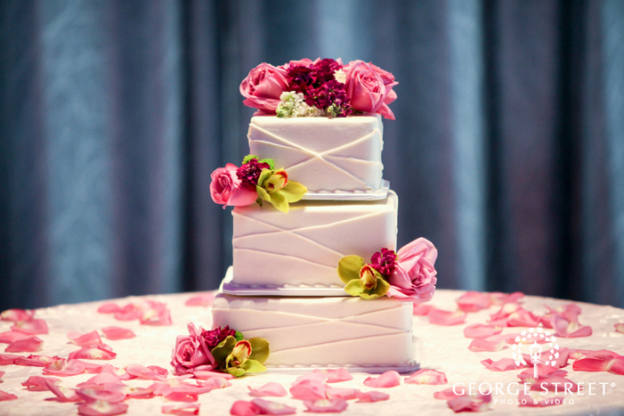 cake with geometric lines and pink flowers on table covered with rose petals