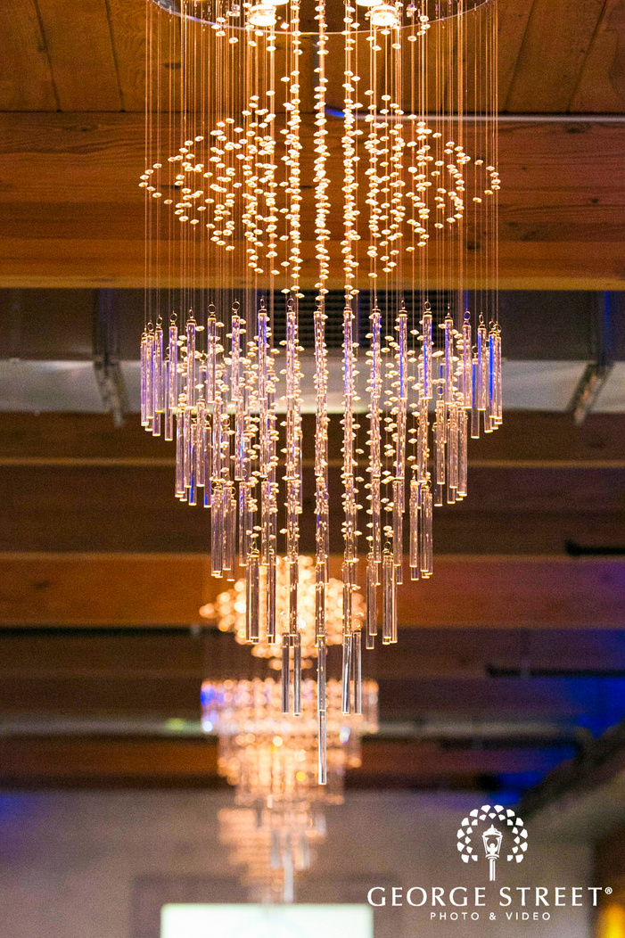 crystal chandeliers in a row under wooden beam ceiling