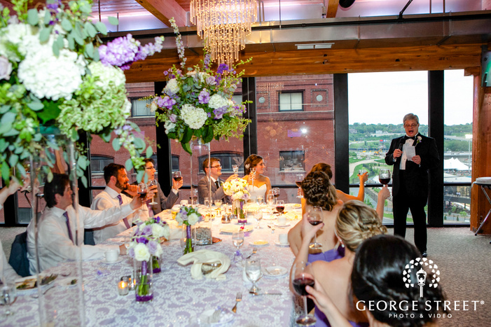 father giving wedding toast to bridal party at reception with large floral centerpieces