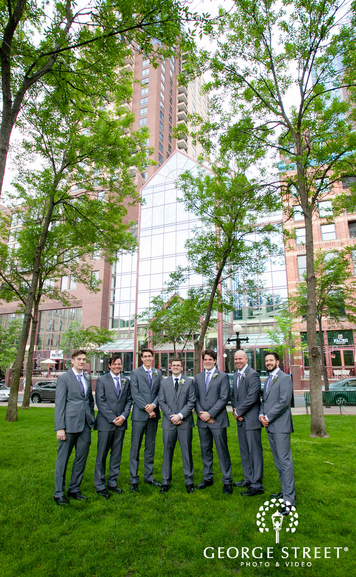 groom and groomsmen standing in front of trees and glass building