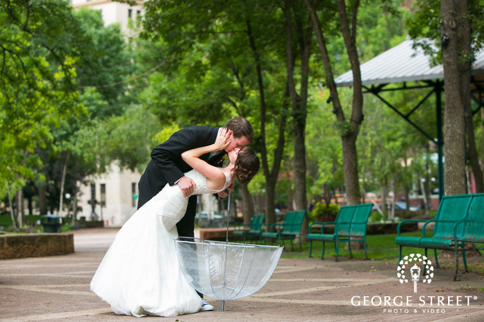 groom holding bride and kissing in outdoor courtyard