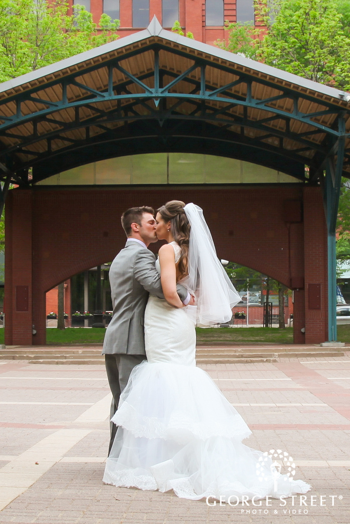 groom with arm around bride kissing in outdoor area