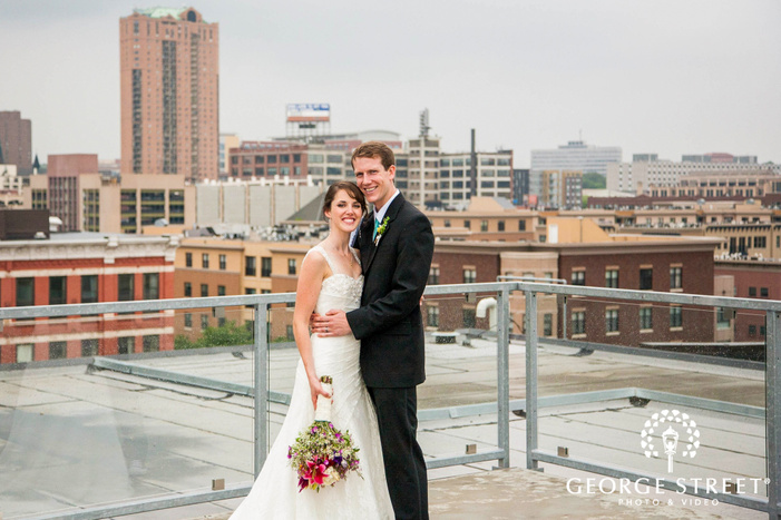 groom with arms around bride smiling on city rooftop