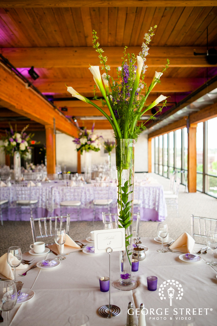tall floral centerpiece on white reception table with purple accents