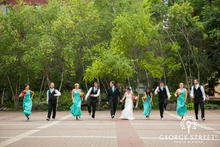 wedding party in long teal dresses and black suits skipping and laughing in outdoor courtyard