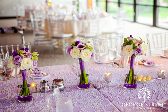white and purple simple bouquets on purple and white embroidered tablecloth