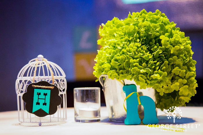 white cage and potted plant with blue letter h reception table decor