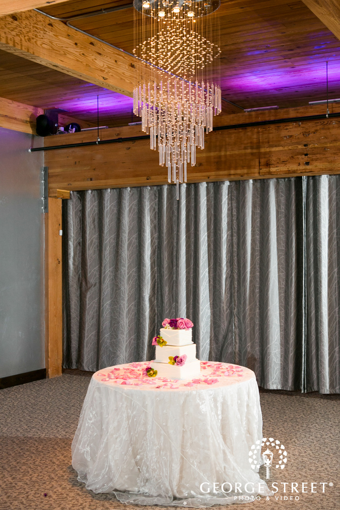 white cake with pink flowers on white cake table underneath chandelier
