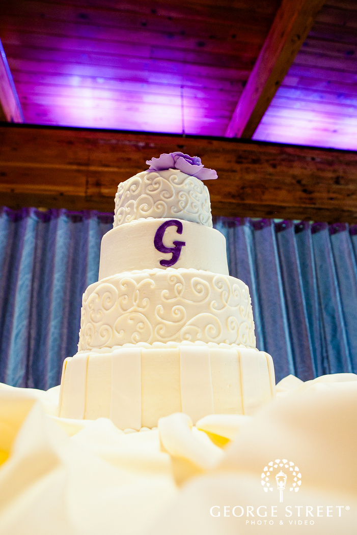 white cake with purple letter G in white table in front of purple wall