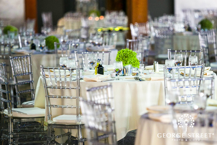 white reception tables with green centerpieces and transparent chairs at ABULAE