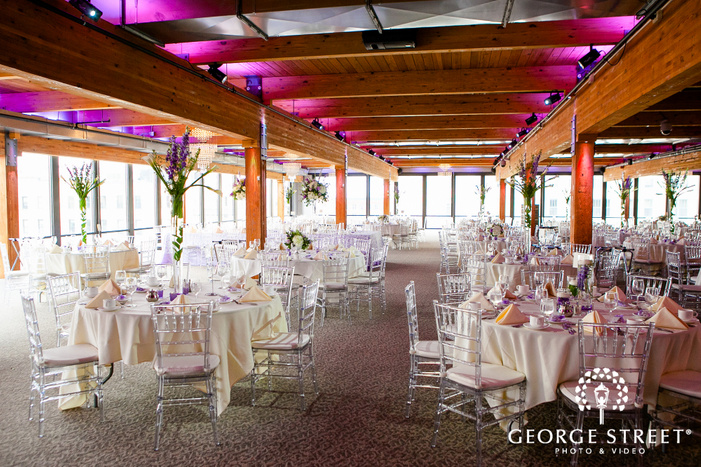 white tables with tall floral centerpieces and transparent chairs with wall of windows and pink lighting