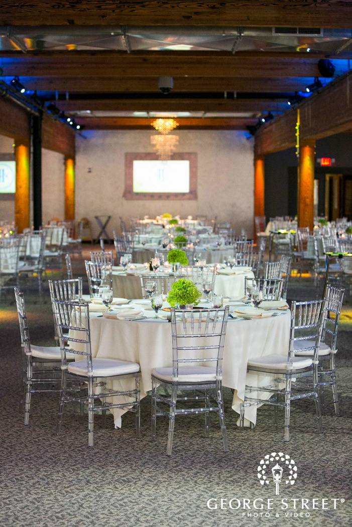 white tables with transparent chairs in bright reception space with wooden beams